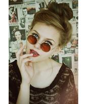 sunglasses,john lennon glasses,amber lens,bun hairsyle,blonde hair,winged liner,pale skin,newspaper/magazine wall