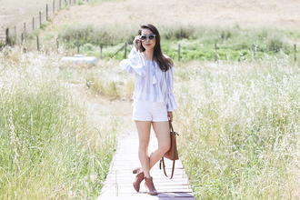 it's not her it's me blogger top shorts bag shoes sunglasses striped off shoulder top blouse bell sleeves bel sleeve top off the shoulder off the shoulder top blue sunglasses boots ankle boots brown boots high heels boots brown bag white shorts