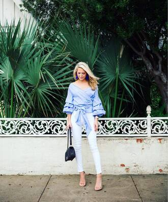 krystal schlegel blogger blouse shoes jeans jewels bag top blue top light blue wrap top puffed sleeves ruffled top ruffle black bag white jeans earrings sandals sandal heels high heel sandals nude sandals