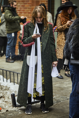 coat wool skirt nyfw 2017 fashion week 2017 fashion week streetstyle green long coat long coat green coat scarf sweater black sweater skirt green skirt wool ruffle maxi skirt sneakers winter outfits winter look