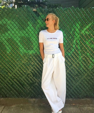 t-shirt white pants flare pants white karlie kloss celebrity model off-duty white t-shirt round sunglasses all white everything celebrity work outfits wide-leg pants pants necklace sunglasses