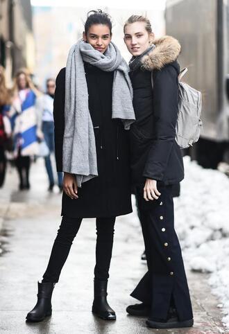 coat nyfw 2017 fashion week 2017 fashion week streetstyle black coat jacket black jacket backpack pants black pants wide-leg pants denim jeans blue jeans skinny jeans black skinny jeans boots black boots flat boots scarf grey scarf
