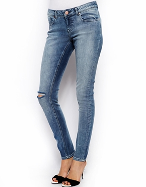 ASOS | ASOS Whitby Low Rise Skinny Jeans in Randolph Mid Wash Blue With Ripped Knee at ASOS