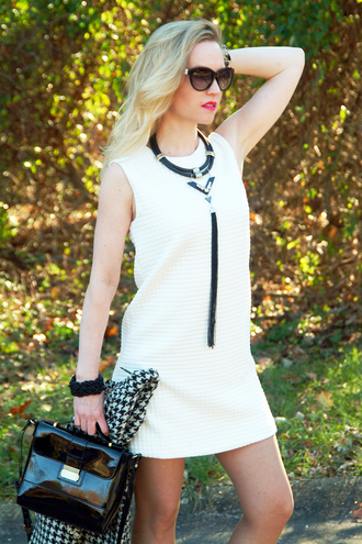 dress jacket short necklace chain blonde hair blogger skinny legs houndstooth shoulder bag patent leather bag white dress mini dress statement necklace black neckalce sunglasses cat eye black bag patent bag