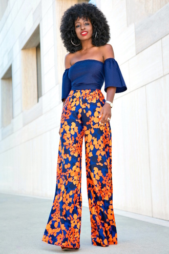 blogger shoes blue top off the shoulder printed pants wide-leg pants floral pants floral blue off shoulder top bell sleeves off the shoulder top hoop earrings earrings curly hair h&m