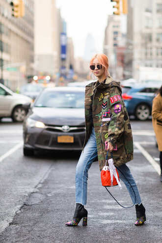 coat nyfw 2017 fashion week 2017 fashion week streetstyle camouflage camo jacket oversized printed oversized coat oversized coat denim jeans blue jeans boots high heels boots printed boots pointed boots bag red bag bucket bag sunglasses orange hair