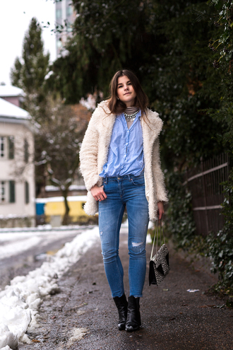 the fashion fraction blogger blue shirt skinny jeans fuzzy coat white fluffy coat fluffy blue jeans denim bag printed bag boots black boots winter outfits winter coat winter look ankle boots cold weather outfit teddy bear coat