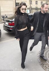 top,Bella Hadid Crop Top,crop tops,black crop top,bella hadid,celebrity,streetstyle,black pants,wide-leg pants,sunglasses,black sunglasses,see through,long sleeves,black blouse