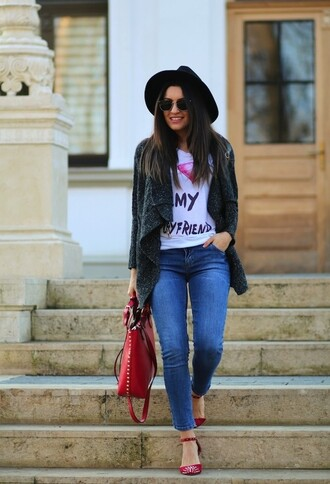 hat white graphic t-shirt skinny jeans black hat red bag red strappy heels sunglasses blogger