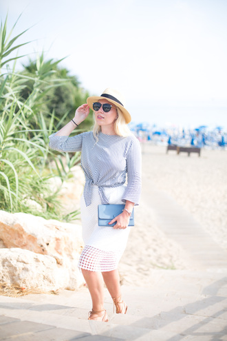 british fashion blog - mediamarmalade blogger skirt blouse bag shoes sunglasses eyelet skirt eyelet detail midi skirt white skirt hat straw hat black sunglasses tie-front top striped top media marmalade bell sleeves clutch blue clutch sandals flat sandals lace up sandals