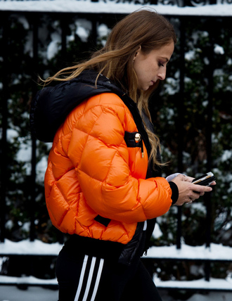 jacket tumblr nyfw 2017 fashion week 2017 fashion week streetstyle orange puffer jacket down jacket pants black pants side stripe pants adidas athleisure