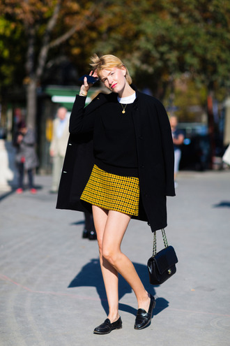 skirt fashion week street style fashion week 2016 fashion week paris fashion week 2016 yellow skirt mini skirt sweater black sweater coat black coat loafers black flats flats black shoes shoes bag black bag fall outfits streetstyle masculine coat french girl style black loafers
