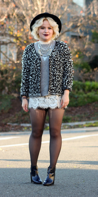 Women's black wool hat, white lace cropped top, black leather belt, black and white boucle jacket, white and black print skater skirt, and charcoal leather ankle boots