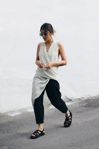 elif filyos blogger dress pants shoes wrap top asymmetrical asymmetrical top sleeveless sleeveless top black pants cropped pants sunglasses sandals black sandals flat sandals