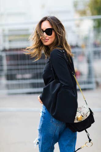 top fashion week street style fashion week 2016 fashion week paris fashion week 2016 black top bell sleeves bag snake print denim jeans blue jeans sunglasses black sunglasses streetstyle song of style blogger