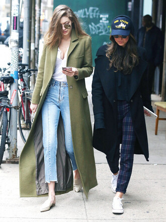 coat tumblr green coat gigi hadid celebrity style celebrity long coat green long coat top white top streetstyle jeans denim blue jeans shoes white shoes pointed flats flats black coat printed pants cap sunglasses mirrored sunglasses