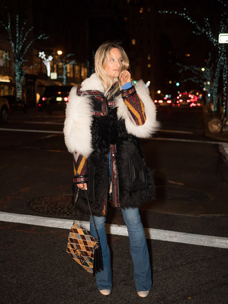 the fashion guitar blogger fur coat flare jeans shoulder bag 70s style winter coat chloe faye bag printed bag purse winter outfits streetstyle trendy big fur coat black coat blue jeans chloe chloe bag printed fur coat