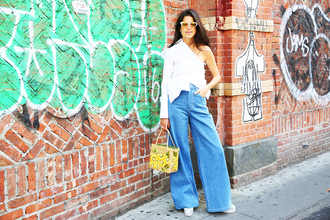 man repeller blogger sunglasses one shoulder white top long sleeves high waisted jeans bell bottoms yellow bag