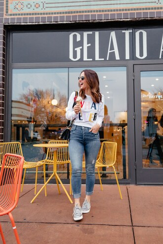 top white top sweatshirt quote on it denim jeans blue jeans skinny jeans sneakers sunglasses