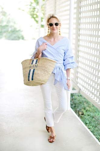 luella & june blogger sunglasses jewels top jeans bag shoes cropped bootcut white jeans white sunglasses white jeans cropped jeans wrap top bell sleeves earrings statement earrings basket bag straw bag hermes shoes hermes slide shoes brown shoes spring outfits blue top