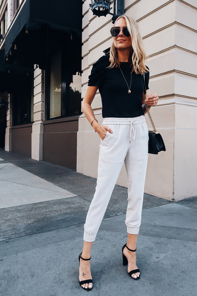 pants joggers white pants high heel sandals black t-shirt shoulder bag aviator sunglasses