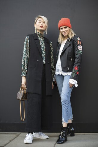 jacket london fashion week 2017 fashion week 2017 fashion week streetstyle black jacket leather jacket black leather jacket embroidered jacket embroidered denim jeans blue jeans cropped jeans beanie blouse white blouse white lace top lace top boots black boots ankle boots thick heel boots sneakers white sneakers pants black pants vest black vest shirt printed shirt bag mini bag earrings jewels jewelry