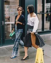 top,asymmetric shirt,white shirt,off the shoulder top,midi skirt,polka dots,side split,pumps,checkered pants,wide-leg pants,flat sandals,clutch