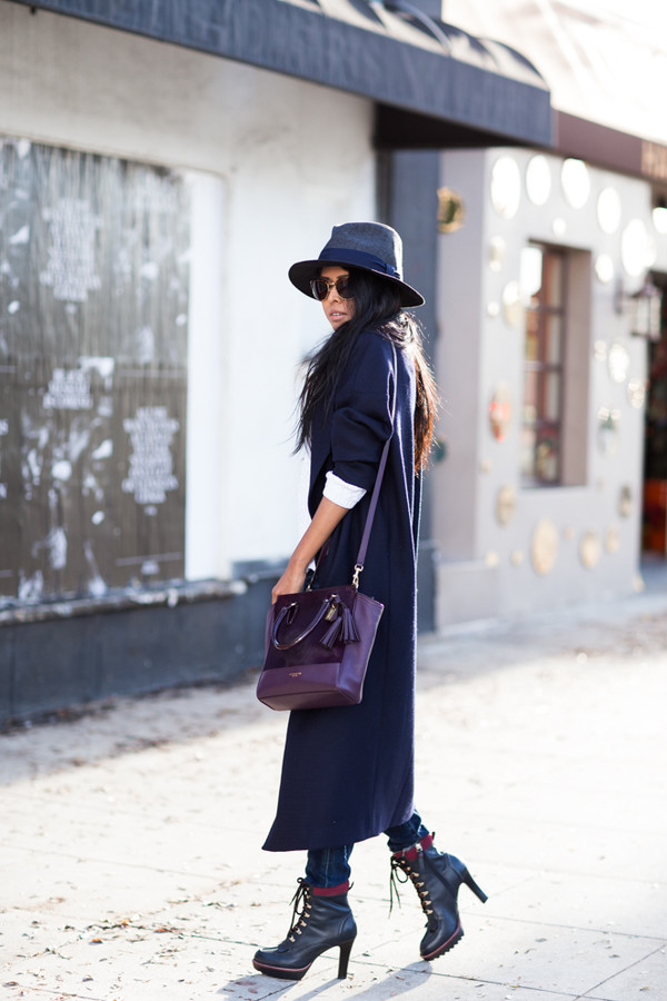 walk in wonderland blogger bag sunglasses long coat fedora black boots plum coat jeans sweater shoes hat jewels blue long coat