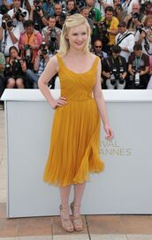 kirsten dunst,stars,celebrity,yellow dress,dress,mustard dress,red carpet dress,pleated dress,midi dress,celebrity style,sandals,sandal heels,high heel sandals,platform sandals,a line dress