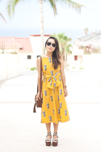 it's not her it's me blogger dress bag jewels shoes yellow yellow dress wedges shoulder bag printed dress midi dress brown bag tassel bag aviator sunglasses summer dress summer outfits sandals wedge sandals yellow midi dress mustard dress