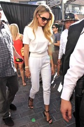 heels,candice swanepoel,white pants,strappy heels,Celebrity work outfits,work outfits,office outfits,celebrity style,white top,slacks,cigarette pants,gold watch,oversized sunglasses