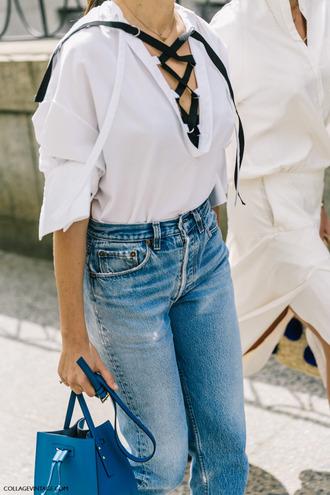 shirt tumblr white shirt lace up top lace up denim jeans blue jeans bag blue bag top fashion week street style fashion week streetstyle white top