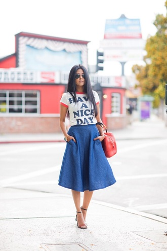 t-shirt flare midi skirt black heels barely there heels blue midi skirt red handbag gold watch streetstyle blogger red tote white t-shirt slogan t-shirts midi skirt black barely there heels aviator sunglasses