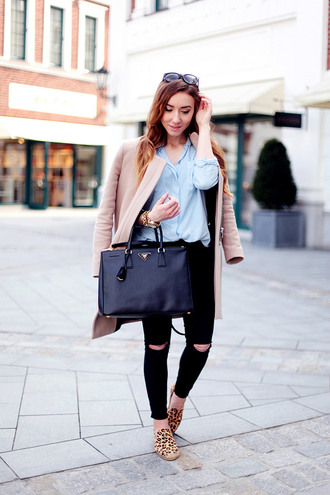 flirting with fashion blogger blue shirt beige coat black ripped jeans slip on shoes leopard print black bag