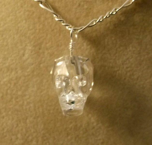 Clear crystal skull charm on silver plated figaro necklace