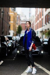 jacket,varsity jacket,fashion week street style,fashion week 2016,fashion week,london fashion week 2016,baseball jacket,teddy jacket,blue jacket,dungarees,overalls,leather overalls,black overalls,sneakers,white sneakers,bag,red bag,fall outfits,streetstyle