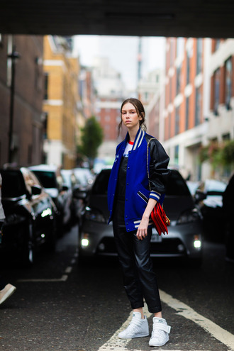 jacket varsity jacket fashion week street style fashion week 2016 fashion week london fashion week 2016 baseball jacket teddy jacket blue jacket dungarees overalls leather overalls black overalls sneakers white sneakers bag red bag fall outfits streetstyle