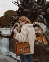 coat,neutral coat,jeans,blue jeans,handbag,brown handbag,bag