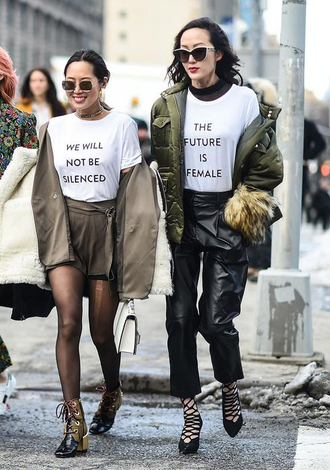 t-shirt nyfw 2017 fashion week 2017 fashion week streetstyle quote on it equality white t-shirt jacket army green jacket pants black pants black leather pants leather pants high heels heels caged sandals boots ankle boots tights shorts blazer sunglasses top blogger lifestyle feminist tshirt