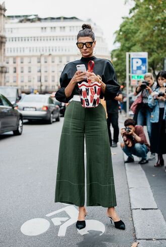 shoes fashion week street style fashion week 2016 fashion week paris fashion week 2016 mules black shoes high heels chanel shoes chanel mules pants wide-leg pants green pants cropped pants top black top oversized sunglasses mirrored sunglasses bag printed bag streetstyle