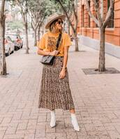 top,printed t-shirt,oversized t-shirt,midi skirt,pleated skirt,leopard print,ankle boots,white boots,crossbody bag,sunglasses,hat