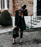 hat,beanie,striped beanie,black beanie,ripped jeans,black jeans,boots,lace up boots,black leather bag,streetstyle,black coat,pom pom beanie