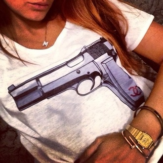 shirt t-shirt clothes white girl hair watch jewels white t-shirt pistol gold white shirt gun cool necklace blouse tshirt gun chanel print white gun print gun top t-shirt dress tshirts chanel top guns and roses dress summer outfits bang bang jewerly print luxury dope fashion style arme blanc tees tshirt.