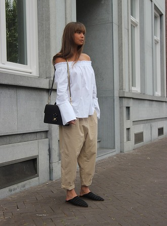 mode d'amour blogger bag off the shoulder long sleeves off the shoulder top white top white blouse black bag shoulder bag nude pants beige pants palazzo pants white off shoulder top bell sleeves bell sleeve top pants slide shoes black slides black babouches babouches spring outfits