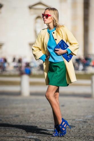 jolie janine blogger yellow coat lemongrass blue sweater blue shoes green skirt red sunglasses blue bag