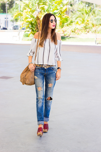 shoes and basics blogger ripped jeans off the shoulder top suede bag mules peasant top striped off shoulder top stripes striped top off the shoulder belt blue jeans bucket bag suede brown bag blue sunglasses spring outfits red mules red shoes