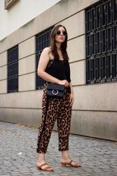 shoes,sandals,animal print,pants,black top,sunglasses,crossbody bag