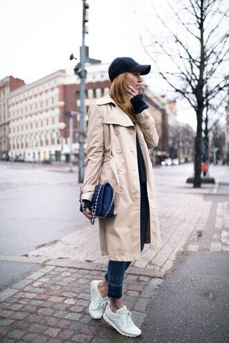 hat black cap trench coat skinny jeans white sneakers blue handbag blogger