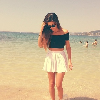 white skirt black crop top off the shoulder beach sea weekend escape mini skirt summer outfits black sunglasses high waisted skirt crop tops summer skater skirt long hair off the shoulder top skirt skirts and tops blouse black top top t-shirt manche epaule noir ete plage magnifique shirt black