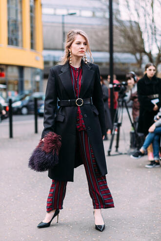 coat london fashion week 2017 fashion week 2017 fashion week streetstyle black coat belt pants printed pants top red top bag furry bag pouch furry pouch pumps pointed toe pumps high heel pumps black heels earrings jewels jewelry